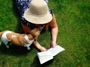 A little dog with a girl reading